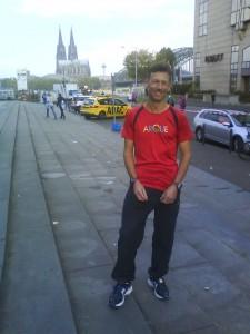 Arno Wenzel mit ARQUE-Shirt, im Hintergrund der Kölner Dom