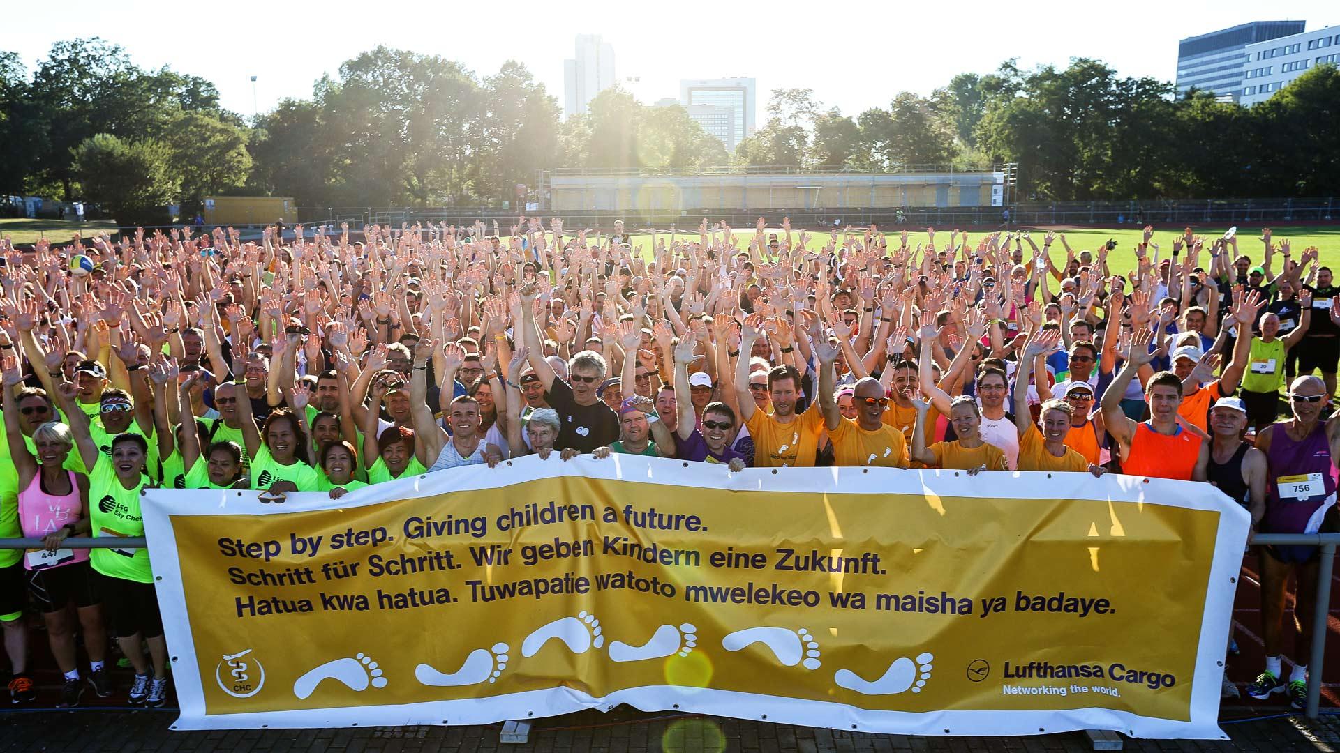 Gruppenfoto vom Bürostadtlauf vor untergehender Sonne mit Banner des Vereins