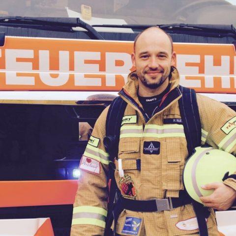 Holger Hüfer vor einem Feuerwehrfahrzeug