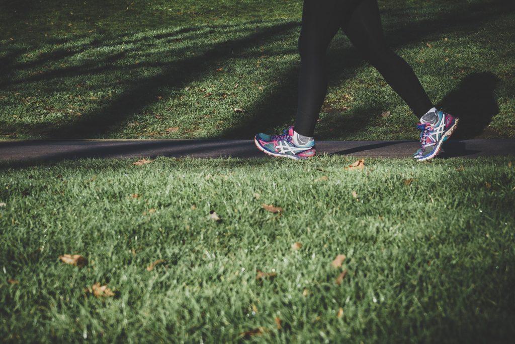 Läufer auf Weg im Gras, Beine und Schuhe im Bild