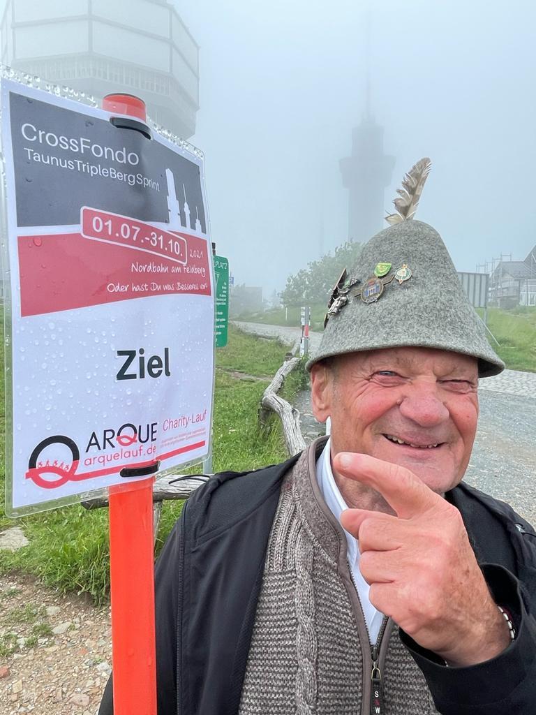 Josef Bachmann vor dem Zielschild des TTBS auf dem Feldberg